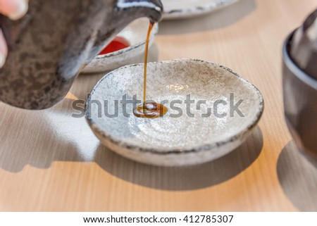 Pour the soy sauce to the bowl  - stock photo