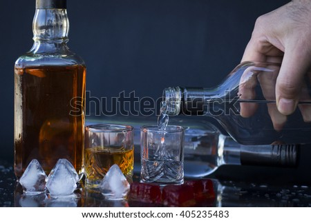 Pour vodka into a glass with ice, vodka and whiskey in glass with ice, alcoholic drink, close-up on a black background - stock photo
