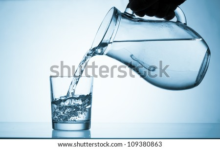 Pour water from a pitcher into a glass - stock photo