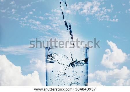 pour water in glass with sky background. - stock photo