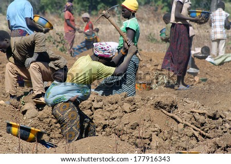 POURA, BURKINA FASO - JANUARY 3: mine in wild golden Poura gold diggers come from everywhere to dig for gold nuggets, a woman and her baby takes all the risks,  january 3, 2008.  - stock photo