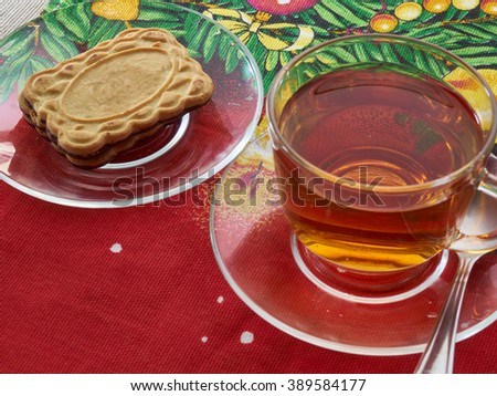 poured into a Cup of hot tea and biscuits on the saucer        - stock photo