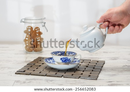 Pouring a cup of tea with cookie jar of gingerbread in the background - stock photo