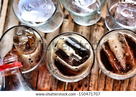Pouring a glass of cola with ice cubes - stock photo