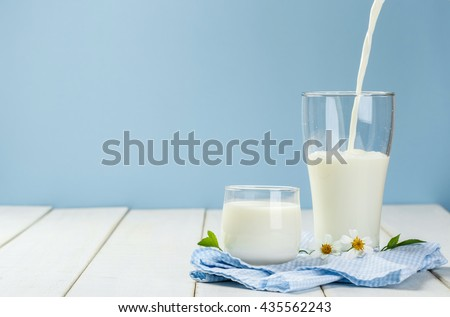 Pouring a glass of milk on a white wooden table on a blue background, tasty, nutritious and healthy dairy products - stock photo