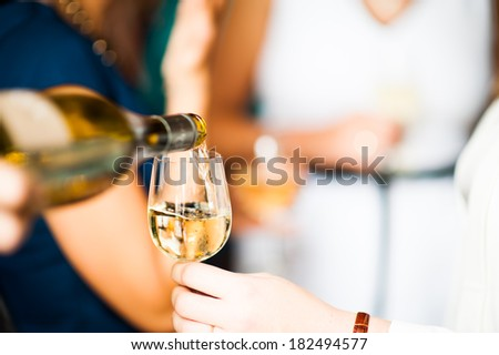 Pouring a glass white wine - stock photo