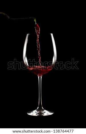 Pouring a red wine glass on black background - stock photo