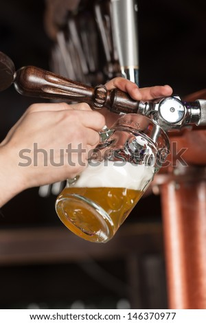 Pouring beer. Close-up of pouring beer at the pub - stock photo