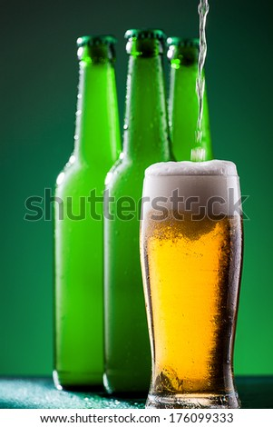 Pouring beer in glass against vivid background - stock photo