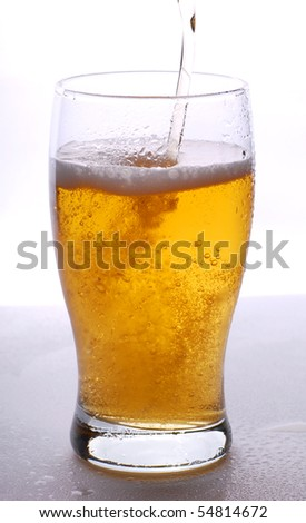 Pouring beer in the glass on white background - stock photo