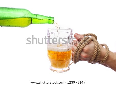 Pouring beer into a mug, motion shot. Bound hands hold a glass. - stock photo
