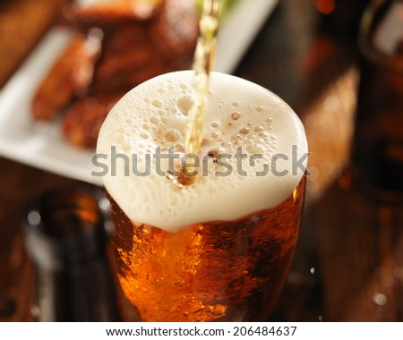 pouring beer into glass with bbq chicken wings in background 01 - stock photo