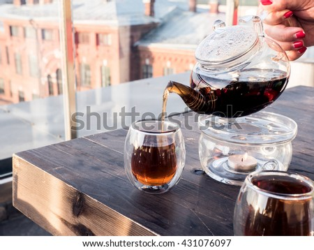 Pouring black tea in a transparent glass, city on a background, female hand holding a transparent teapot - stock photo