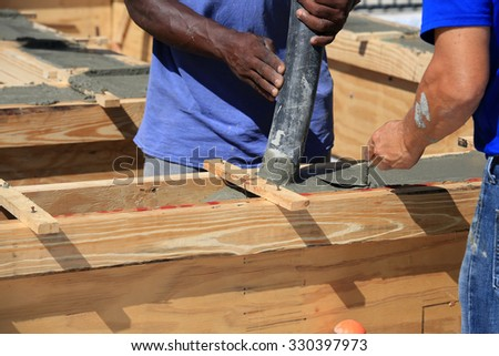 Pouring cement for a tie beam on a concrete block wall. - stock photo