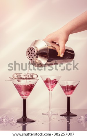 Pouring cocktail drinks from a shaker into Art Deco cocktail glasses - stock photo