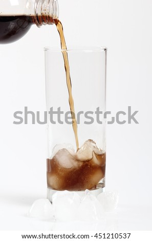Pouring cola from plastic bottle into glass with ice cubes. Isolated on white background. - stock photo