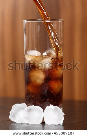 Pouring cola into glass with ice cubes - stock photo