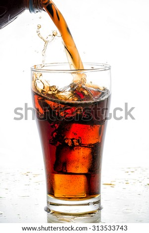 Pouring cola into glass with ice cubes, on white background - stock photo