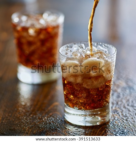 pouring cola soda pop into cup - stock photo