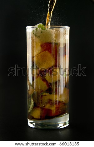 Pouring cola to the glass ice and mint on black background. - stock photo