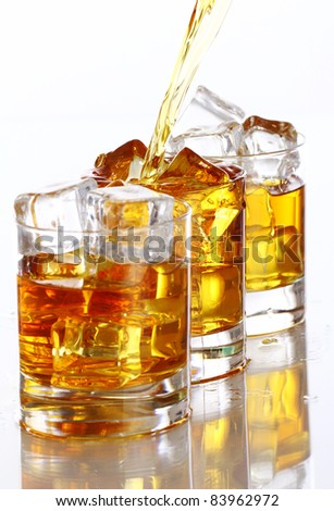 Pouring cold whiskey into the glass isolated over white background - stock photo
