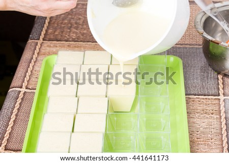 Pouring dough into plastic baking forms. Macro. Photo can be used as a whole background. - stock photo