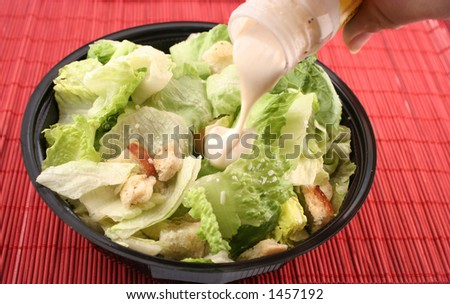 pouring dressing over lettuce for a caesar salad - stock photo