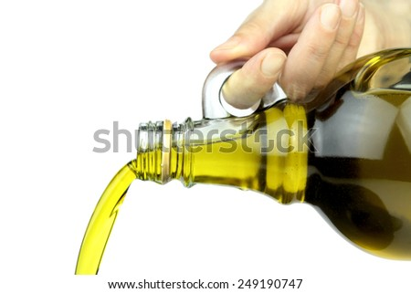 Pouring extra virgin olive oil from glass bottle - stock photo