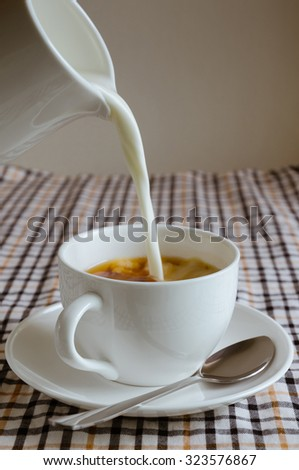 Pouring Fresh Milk Into a Cup of Tea. - stock photo