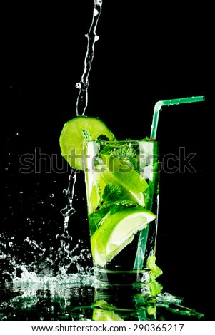 Pouring fresh mojito cocktail in glass isolated on black background - stock photo