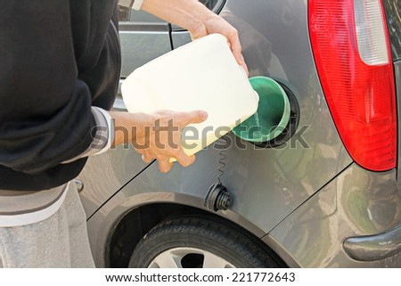 pouring gasoline into the gas tank from a white canister - stock photo