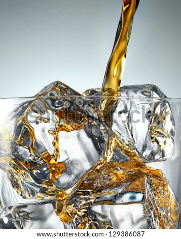 Pouring Glass of scotch whiskey and ice - stock photo