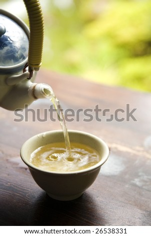 Pouring Green Tea from Pot into Cup - stock photo