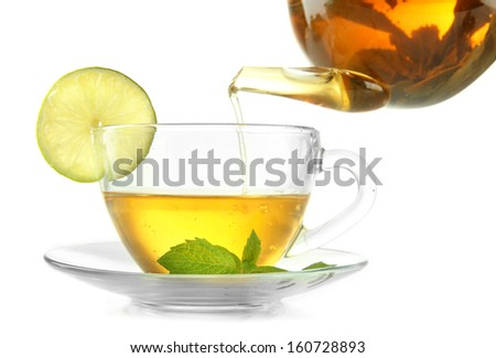 Pouring green tea into cup isolated on white - stock photo