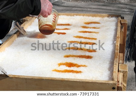 Pouring Hot Maple Syrup Onto Snow To Make Maple Taffy A Sweet Treat On A Popsicle Stick - stock photo