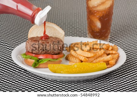 Pouring ketchup onto a hamburger with fries, pickle and a drink - stock photo