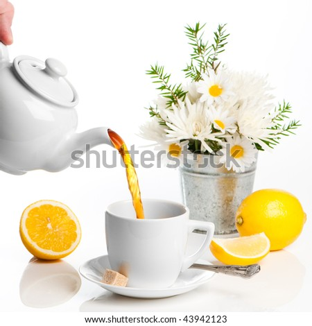 Pouring lemon tea from white teapot with vase of flowers in background - stock photo