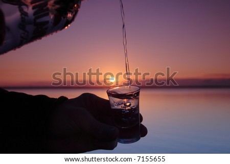 Pouring liquid into a shot glass against sunset - stock photo