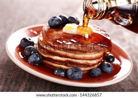 Pouring maple syrup on stack of pancakes - stock photo