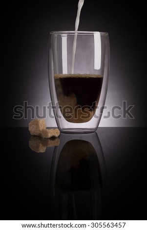 Pouring milk into filter coffee in glass on dark black background. Delicious coffee drinking. - stock photo