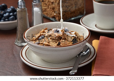 Pouring milk onto a bowl of bran flakes, high speed photography - stock photo