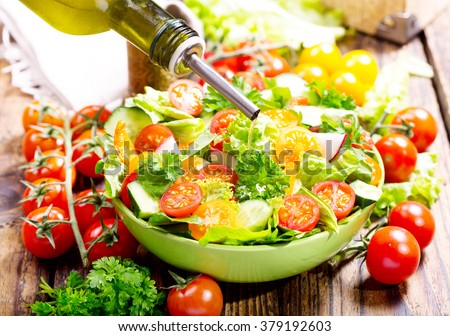 pouring oil into bowl of salad with vegetables - stock photo