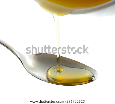 Pouring oil on spoon isolated on white,Selective focus on a spoon - stock photo