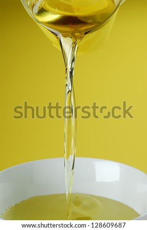 Pouring oil on yellow background - stock photo