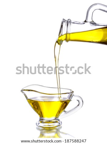 Pouring olive oil from glass bottle to gravy boat, isolated white background  - stock photo