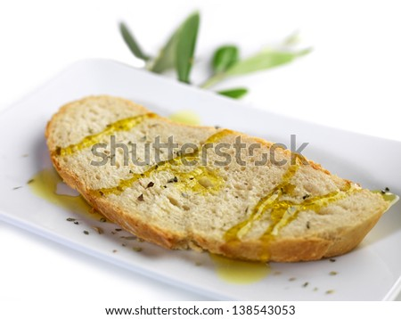 pouring olive oil on a slice of bread with oregano - stock photo