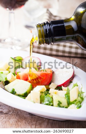 pouring olive oil over salad  - stock photo