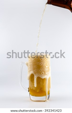 Pouring process of lager beer into a beer glass mug, splashes, drops and froth around glass mug against white background - stock photo