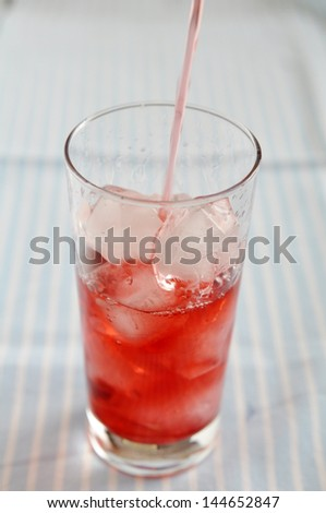 pouring red drink into the glass - stock photo