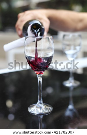 Pouring red wine from bottle into the wineglass in outdoor restaurant - stock photo